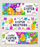 Easter greeting banners. Colorful marmalade and candys in the shape of rabbits, chickens, eggs and other forms. On a multicolored paper background Royalty Free Stock Photography
