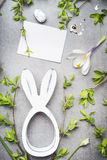 Easter greeting with blank white card , eggs, spring twigs , flowers and bunny decor Stock Photo