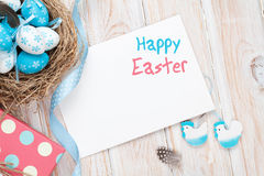 Easter greeting card with blue and white eggs and gift box over Royalty Free Stock Photo