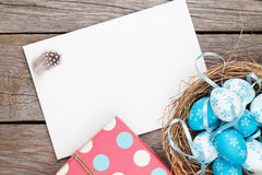 Easter greeting card with blue and white eggs and gift box over Stock Images