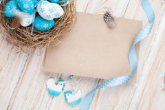 Easter greeting card with blue and white eggs in nest and decor Royalty Free Stock Photos
