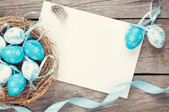 Easter greeting card with blue and white eggs in nest over wood. Top view with copy space Royalty Free Stock Photography