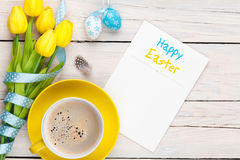 Easter greeting card with blue and white eggs, yellow tulips and Stock Photography