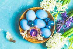 Easter greeting card with colored blue eggs. Quail eggs and candles in wooden plate in front of white and blue hyacinths over blue concrete surface background stock photography