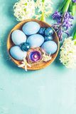 Easter greeting card with colored blue eggs. Quail eggs and candles in wooden plate in front of white and blue hyacinths over blue concrete surface background stock photo