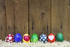 Easter greeting card with colorful different eggs on wood. Royalty Free Stock Photo