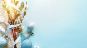 Easter greeting card with colorful easter eggs and sprin flowersl on blue table. Top view with space for your greetings - Image stock photography