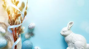 Easter greeting card with colorful easter eggs and sprin flowersl on blue table. Top view with space for your greetings - Image royalty free stock images