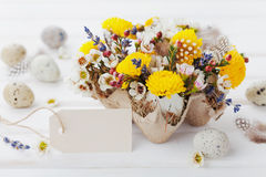 Easter greeting card with colorful flowers, paper tag, feather and quail eggs on rustic white table. Beautiful spring composition. Royalty Free Stock Photo