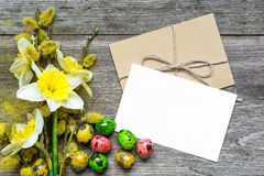 easter greeting card with easter eggs, daffodil flowers and blooming willow branches