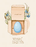 Easter greeting card with egg in a box, flowers on beige background. Royalty Free Stock Photos