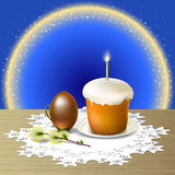 Easter greeting card. Easter egg and Easter cake on white plate are on wooden table covered white openwork napkin. Small light shine on candle standing on Easter Royalty Free Stock Photo