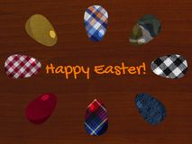Easter greeting card with fabric textured eggs on the wooden background royalty free stock image