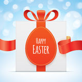 Easter greeting card with a gift box. White gift box with egg shaped tag, tied with a red ribbon on a blue bokeh background. Easter greeting card vector design Royalty Free Stock Image