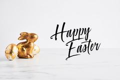 Easter greeting card, golden rabbit and eggs decorated with golden foil stock image