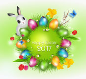 Easter greeting card 2017. Grass circle with bright colorful eater eggs on blue background decorated with spring flowers and easter bunny Royalty Free Stock Photos