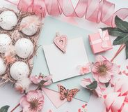 Easter greeting card mock up with eggs box, pink ribbon, gift box and flowers decoration. Top view, pastel color Stock Photography