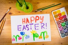 Easter greeting card with paintbrush and palette  at the table Stock Photos