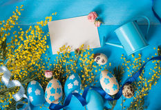 Easter greeting card. Painted eggs with yellow mimosa flowers and tiny watering can Stock Image