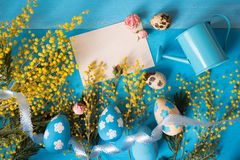 Easter greeting card. Painted eggs with yellow mimosa flowers and tiny watering can Royalty Free Stock Images