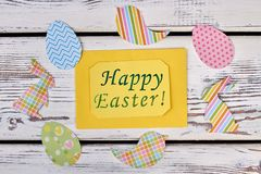 Easter greeting card and papercut figures. Yellow Easter greeting card and composition of animalistic paper cutouts on white wooden background, top view stock photos