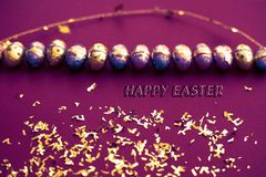 Magenta tinted easter background. Golden confetti on colored sheets. Easter golden egg on surface.Top view of decor arrangements. stock images