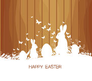 Easter greeting card with rabbit, gift and lights on the wooden background Stock Photos