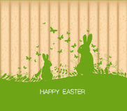 Easter greeting card with rabbit, gift and lights on the wooden background Royalty Free Stock Photography