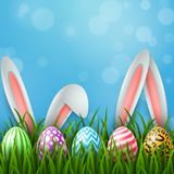 Easter greeting card with two bunny ears and colorful eggs on blue background Royalty Free Stock Photo
