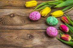 Easter greeting with eggs and yellow red tulips royalty free stock photography