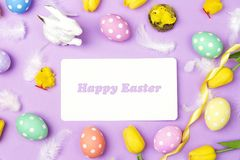 Easter greeting message with colored eggs, feathers and tulip on Stock Image