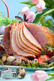 Easter ham. Honey ham on Easter table with quail eggs, tulips and decoration stock photos