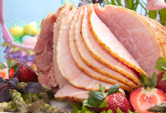 Easter ham. Honey ham on Easter table with eggs, flowers and decoration Stock Images