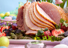 Easter ham. Honey ham on Easter table with eggs, flowers and decoration Stock Photo