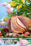 Easter ham. Honey ham on Easter table with quail eggs, tulips and decoration royalty free stock image