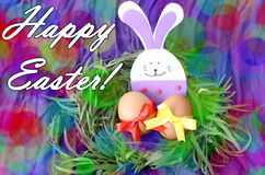 Easter hand made decorated greeting card: yellow eggs and hand made festive plastic foam bunny in green grass twigs nest on purple Stock Photography