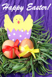 Easter hand made decorated greeting card: yellow eggs and hand made hatched chicken in eggshell in green grass twigs nest on purpl Royalty Free Stock Images