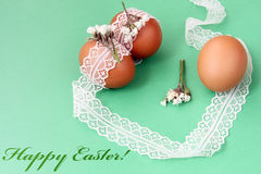 Easter hand made decorations: easter eggs with white lace isolated on green background Royalty Free Stock Photography