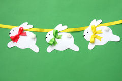 Easter hand made decorations: festive paper bunny garland isolated on green background Royalty Free Stock Image
