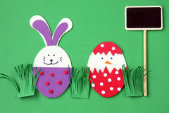 Easter hand made decorations: festive plastic foam bunny and egg with blackboard isolated on green background Royalty Free Stock Photo