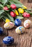 Easter. Hand made easter eggs and spring tulips on old wooden table Stock Photography
