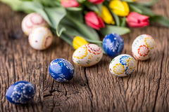 Easter. Hand made easter eggs and spring tulips on old wooden table Stock Photos
