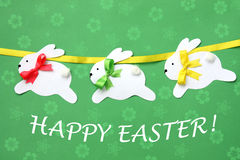 Easter hand made greeting card: festive paper bunny garland isolated on flower background Stock Photos