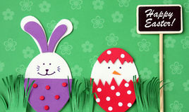 Easter hand made greeting card: festive plastic foam bunny and egg with blackboard isolated on flower background Stock Photos