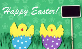 Easter hand made greeting card: hatched chicken in eggshell with blackboard isolated on flower background Stock Image