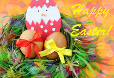 Easter hand made greeting card: yellow eggs and hand made hatched chicken in eggshell in green grass twigs nest on bright colorful Royalty Free Stock Images