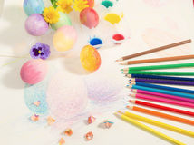 Easter hand-painted eggs with colored pencils,watercolors and spring flowers,arranged on colored drawing. Stock Image