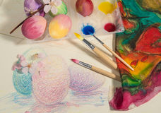 Easter hand-painted eggs with painter brushes,colorful cloth,watercolors and almond blossom,arranged on a colored drawing. Stock Photography
