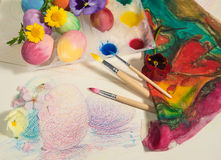 Easter hand-painted eggs with painter brushes,colorful cloth,watercolors and almond blossom,arranged on a colored drawing. Royalty Free Stock Image