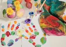 Easter hand-painted eggs with painter brushes,colorful cloth,watercolors and spring flowers ,arranged on colored fingerprints. Royalty Free Stock Photos
